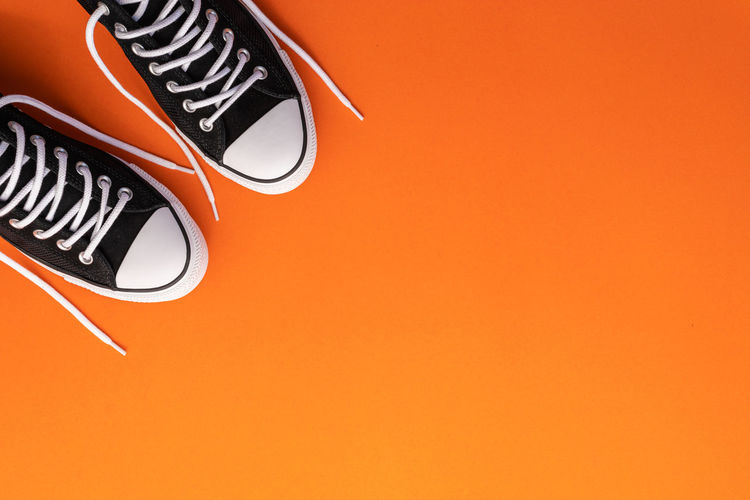 High angle view of black shoes on orange background