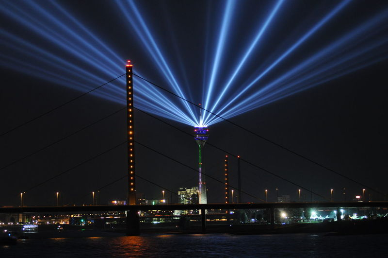Rheinkniebrucke over rhine river against illuminated rheinturm tower at night