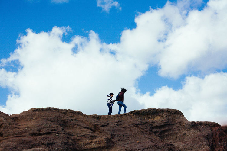 Low angle view of men standing on rock against sky