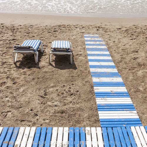 High angle view of empty lounge chairs at beach