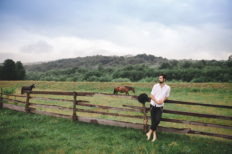 Portrait of a handsome man in a white shirt and black trousers. His hat hangs on a wooden fence next to him. The guy leans on the fence. This is the groom. He has a beautiful face, he wears a beard. At the guy the attractive harmonous figure. He stands on the green grass in the middle of the meadow. In the background, there are mountains and sky with clouds. The horse graces the portrait in full growth. Shooting with daylight. Fashion Nature Standing Animal Animal Themes Barrier Boundary Day Domestic Domestic Animals Environment Fence Field Grass Herbivorous Horse Land Landscape Livestock Mammal Nature One Person Outdoors Plant Real People