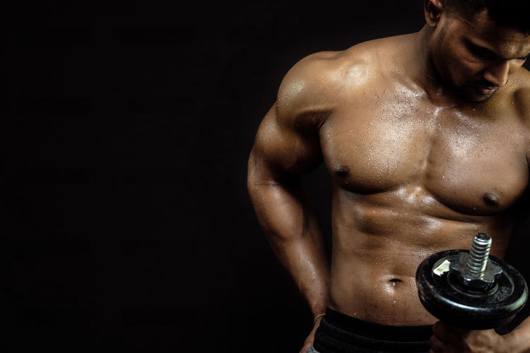 Young man holding dumbbell against black background