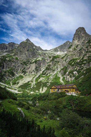 Scenic view of house and mountains against sky