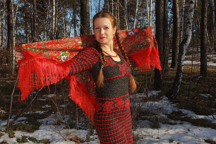 Portrait of woman standing in forest during winter