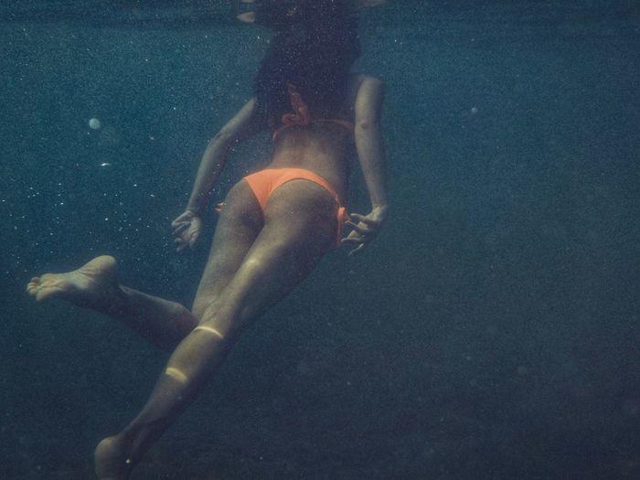 Rear View Of Woman Wearing Bikini Swimming In Sea