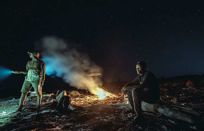 People sitting on bonfire against sky at night