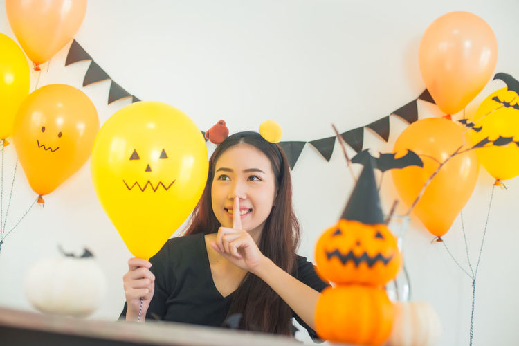 Woman looking at balloon during halloween celebration