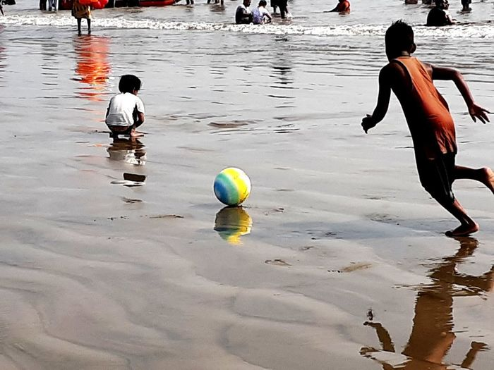 People playing soccer ball on beach