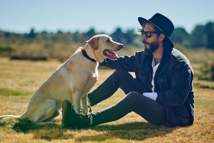 Man with dog sitting on field