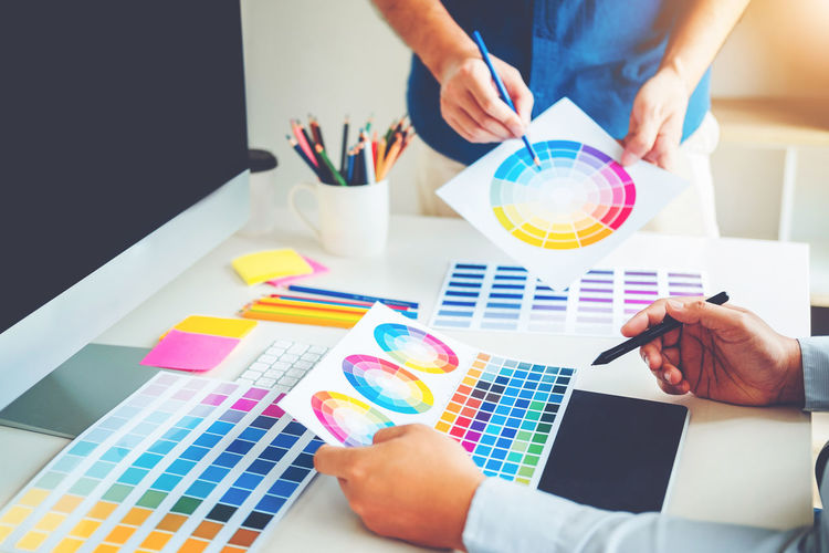 Design professionals pointing at color swatch on table
