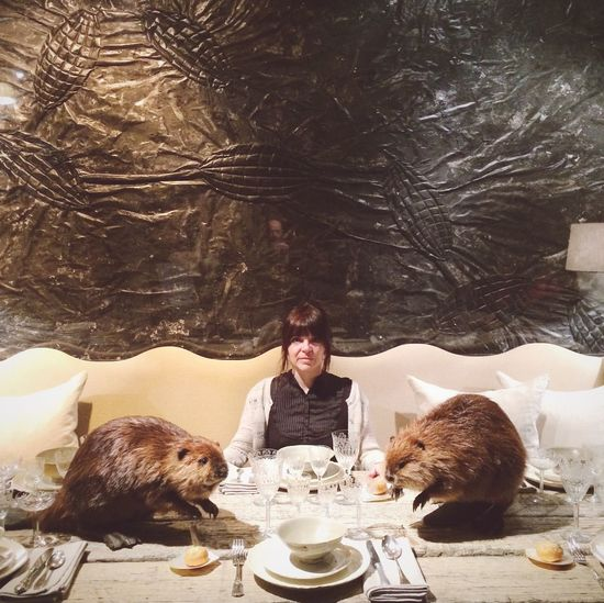 Portrait of woman with animals at dining table