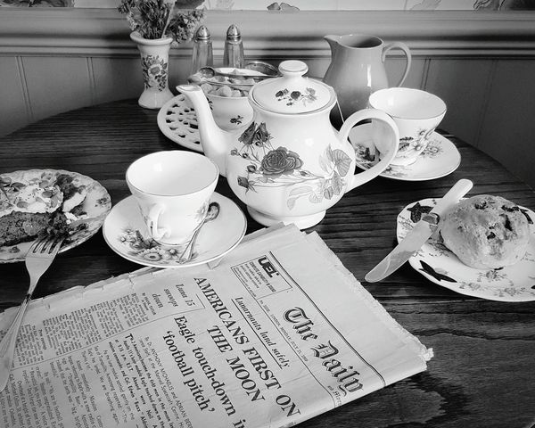 Food And Drink Freshness Table Indoors  Plate Still Life Food Flower Large Group Of Objects Retail  Ready-to-eat English Tradition Cakes Teatime Old Newspaper Beverage Food And Drink Indoors  Freshness Refreshment Drink Selective Focus Black & White No People Blackandwhite Photography
