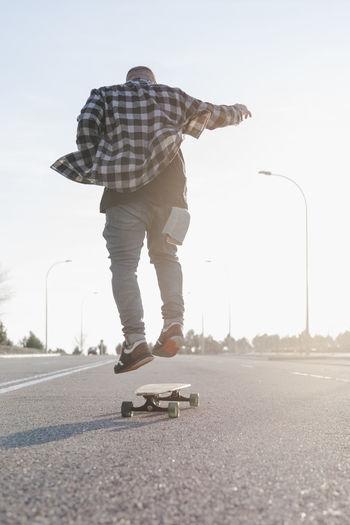 Rear view of man skateboarding on road