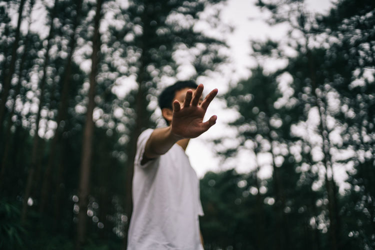 Low angle view of boy showing stop gesture against trees