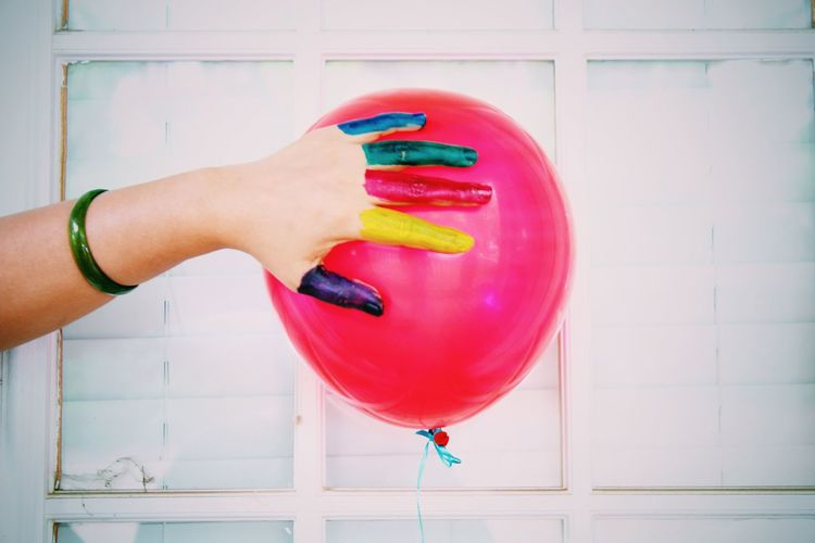 Cropped colorful watercolor paints covered hand touching red helium balloon
