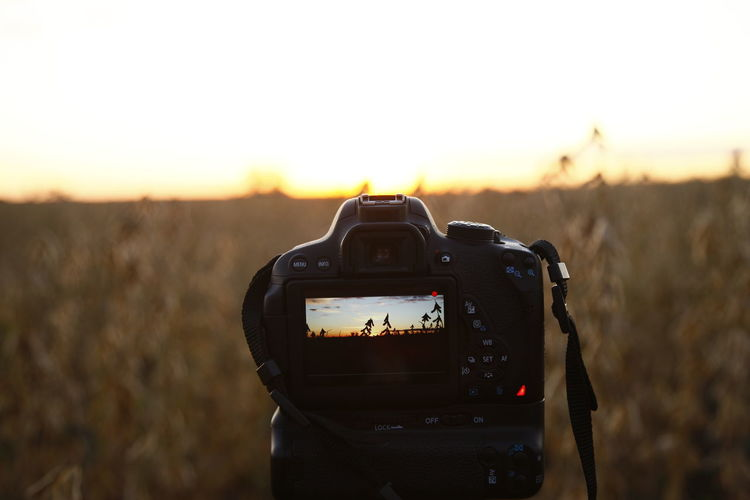 Close-up of camera on field against sky during sunset