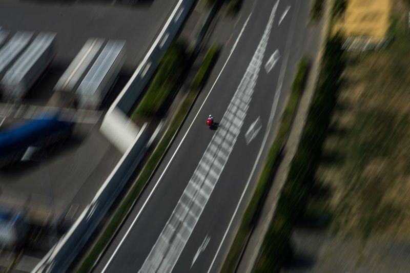 郵便局員 Postman High Angle View Transportation Motion Blurred Motion Architecture Day One Person Outdoors Road Symbol Land Vehicle Road Marking Real People City on the move #urbanana: The Urban Playground