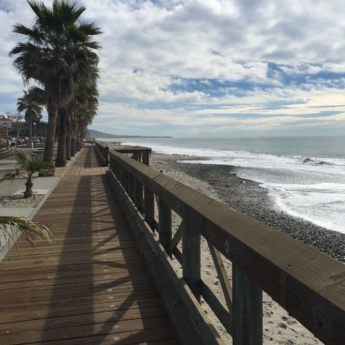 Capistrano Beach Boardwalk Sea Beach Water Sand Nature Shore Beauty In Nature Scenics Outdoors Palm Tree Railing Sky Wave Trees Boardwalk No People Day Orange County San Juan Capistrano Beaches Beachphotography Beach Photography Beach Life Clouds And Sky Clouds