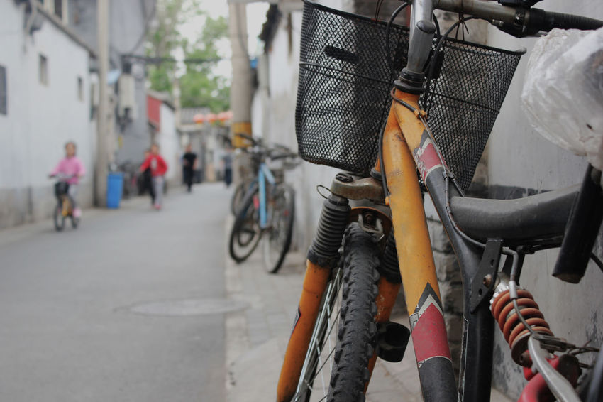 Architecture Bicycle City Close-up Day Focus On Foreground Hutong Hutong Life Hutong Street Incidental People Land Vehicle Mode Of Transportation Outdoors Parking People Real People Road Scooter Sport Stationary Street Transportation Travel Wheel Summer Road Tripping