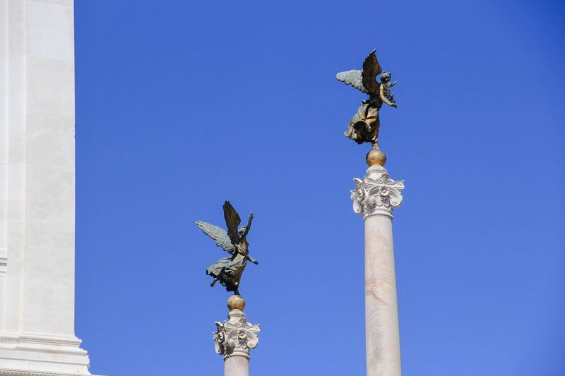 Low Angle View Of Columns Against Clear Blue Sky On Sunny Day