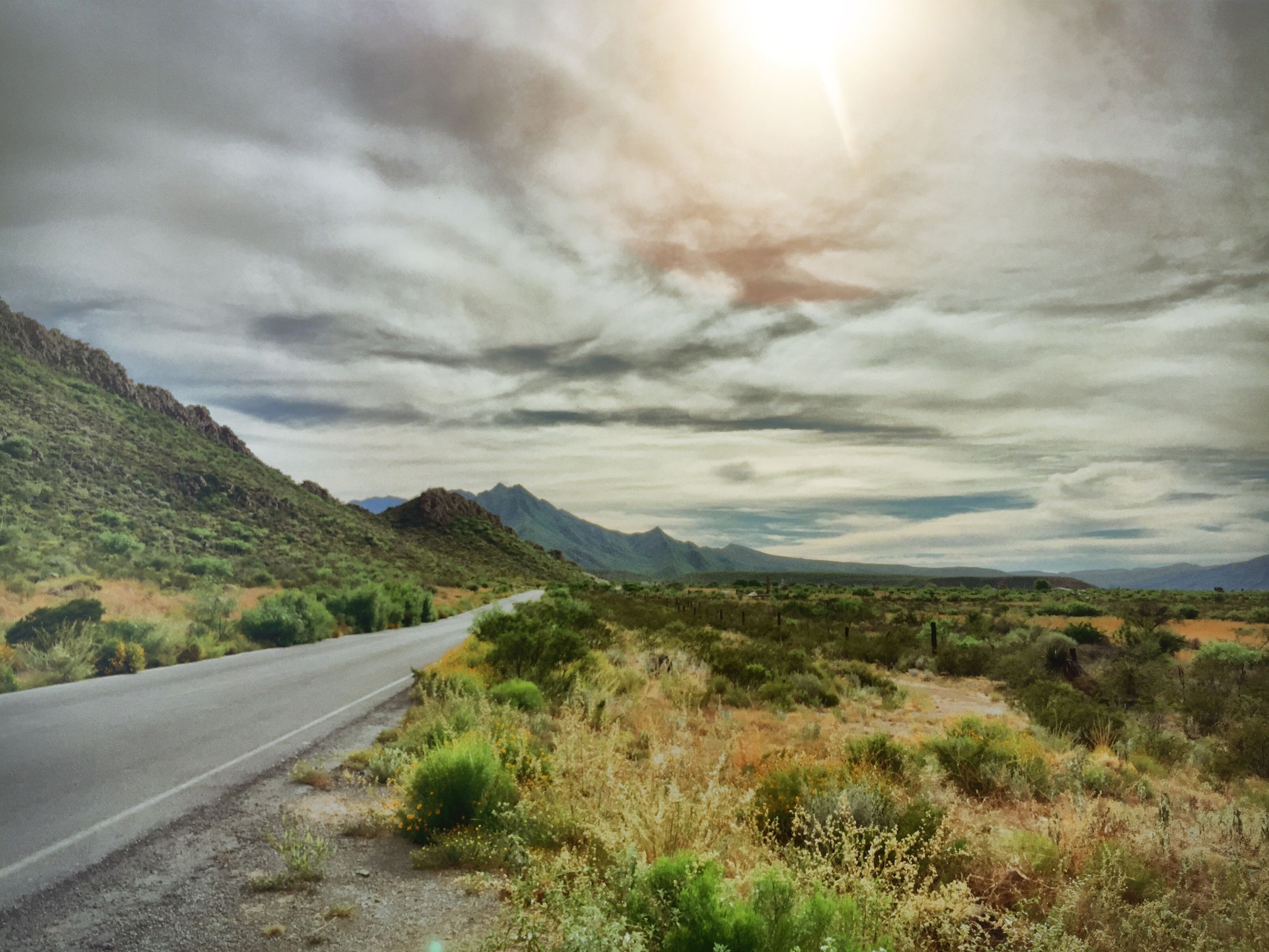 road, the way forward, sky, transportation, mountain, landscape, cloud - sky, tranquil scene, country road, tranquility, scenics, nature, grass, road marking, beauty in nature, cloudy, diminishing perspective, non-urban scene, cloud, empty road