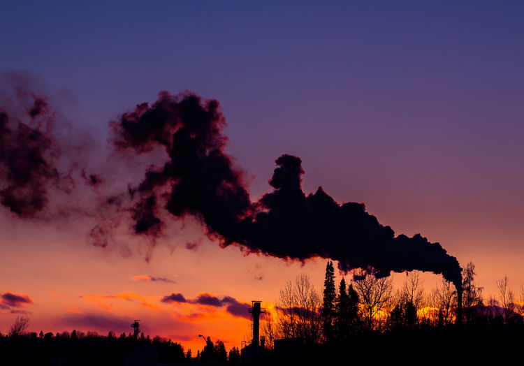 Factory Emitting Smoke In Sky At Sunset