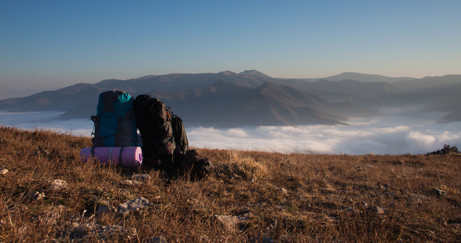 Backpacks On Mountain Against Cloudscape