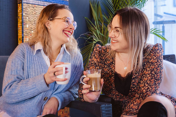 Young women talking while holding coffee