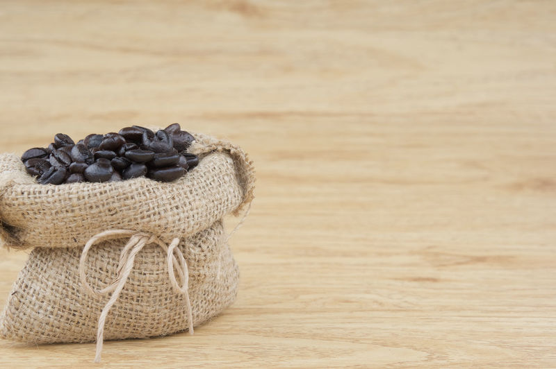 Close up stack of coffee bean in brown sack place on wooden background. Agriculture Caffeine Coffee Espresso Mocha Stack Toasted Wood Abundance Background Bag Bean Black Brown Close-up Copy Space Food And Drink Freshness Pile Roasted Sack Still Life Studio Shot Table Wooden