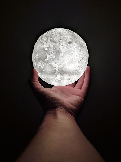 Close-up of hand holding crystal ball against black background