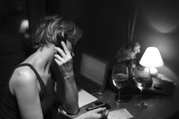 Woman listening to mobile phone while writing on paper at home