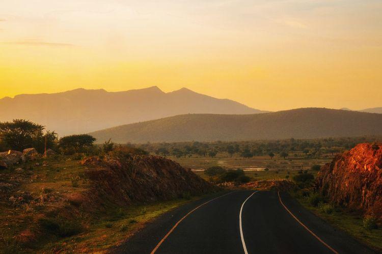 An empty highway against a golden sunset at iringa, tanzania