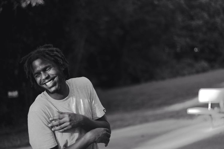 Smiling Young Man With Dreadlocks At Park