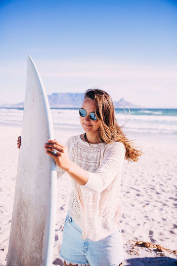 Leisure Activity Sea One Person Water Lifestyles Real People Sunglasses Glasses Beach Young Adult Casual Clothing Young Women Fashion Sky Nature Standing Hairstyle Hair Outdoors Horizon Over Water Surfboard Surfing