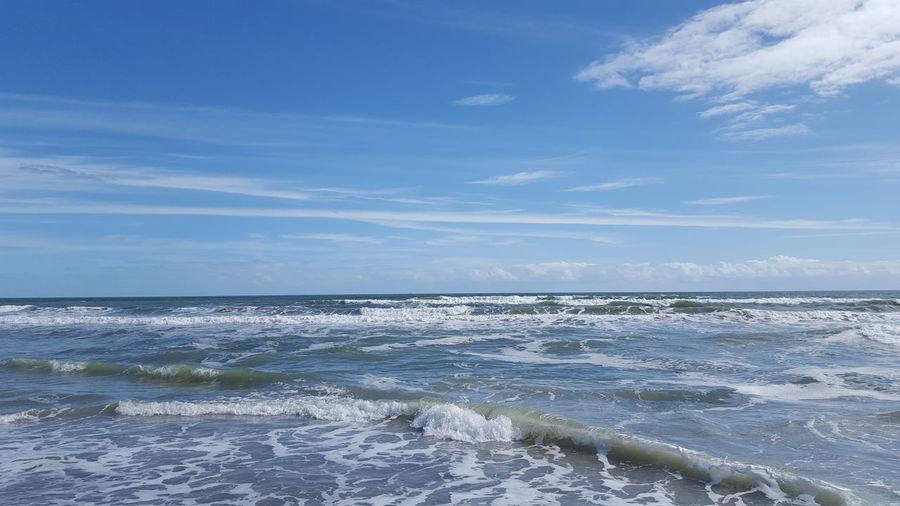 Waves splashing in sea against cloudy sky