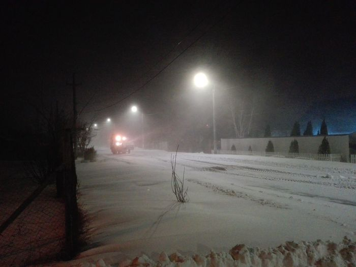Snow covered street lights at night