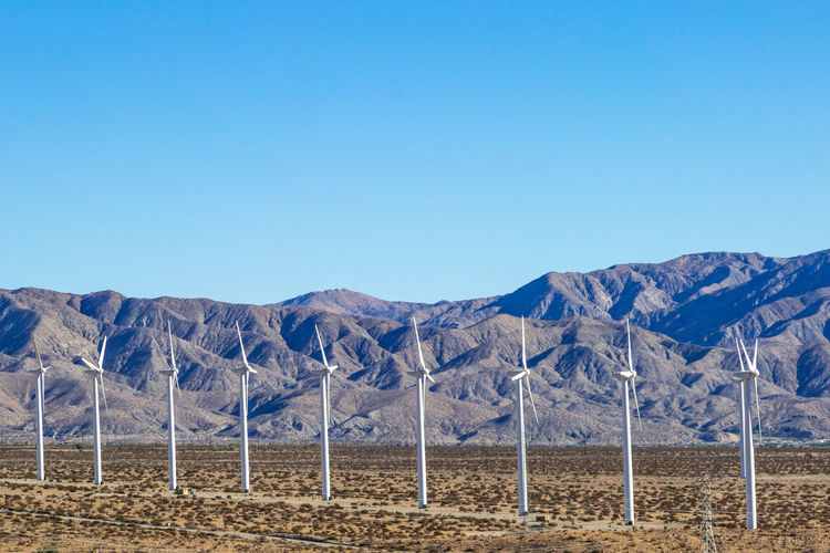 Wind Turbines in a Row in the Californian Desert Mountain Sky Scenics - Nature Tranquil Scene Clear Sky Copy Space Beauty In Nature Environment Blue Tranquility Landscape Nature Non-urban Scene Land No People Mountain Range Idyllic Day Remote Outdoors Arid Climate Climate Formation Wind Power Wind Farm