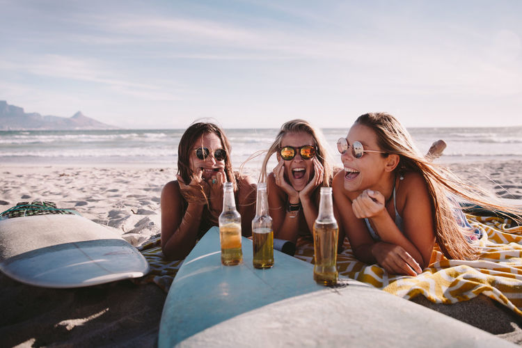 Panoramic view of friends drinking water on beach