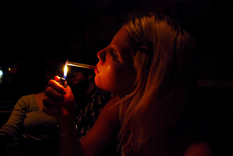 Close-Up Of Young Woman Lighting Cigarette With Lighter In Bar