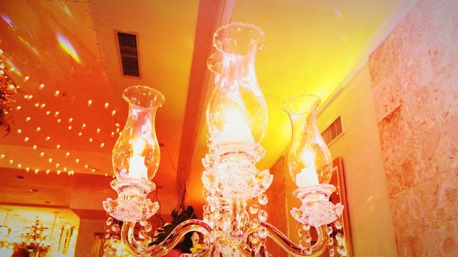 Low angle view of illuminated chandelier hanging on wall