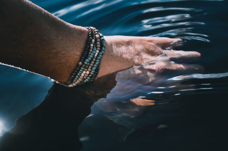 Close-up of hand by sea