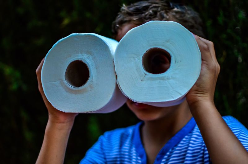 Boy with face covered by toilet papers