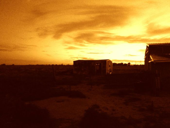 Built structure on landscape at sunset
