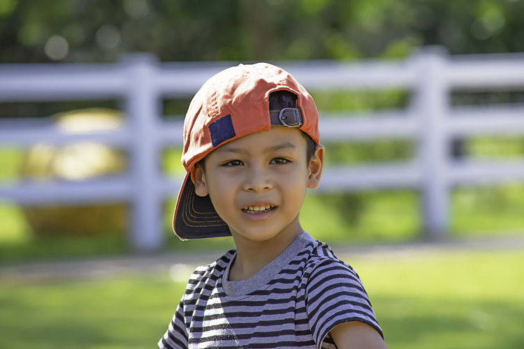 Close-up portrait of cute boy wearing cap standing outdoors