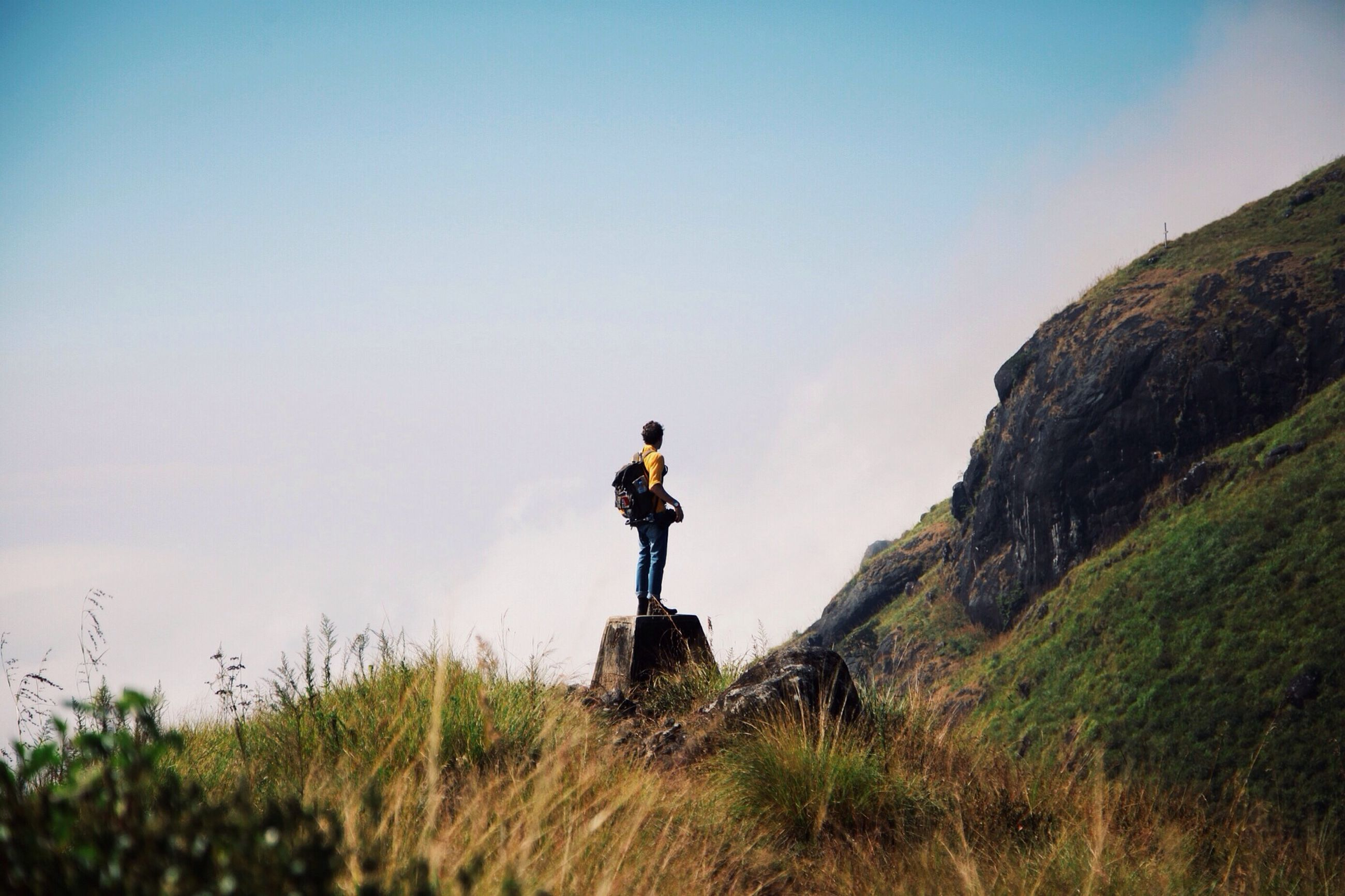 lifestyles, full length, leisure activity, casual clothing, clear sky, standing, men, mountain, rear view, copy space, nature, rock - object, photography themes, young men, landscape, camera - photographic equipment, beauty in nature, backpack