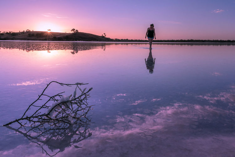 Woman walking in lake against sky during sunset