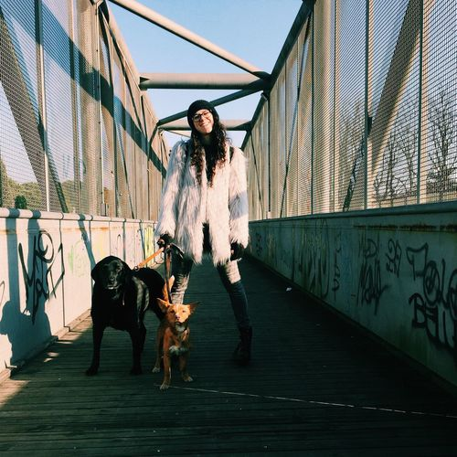 Woman standing on footbridge with dog