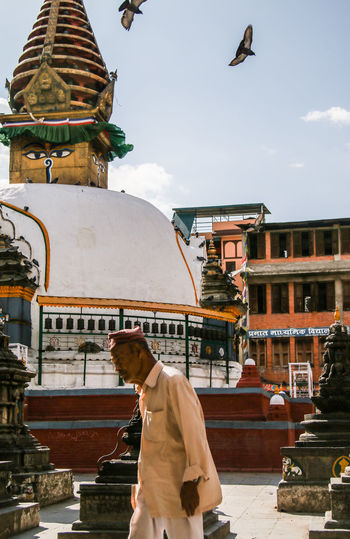 Low angle view of man outside temple against building