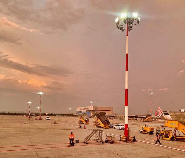 Italy, at Verona VRN Int'l airport, a few minutes before sunset Sunset Tarmac Incidental People Incidental Person Unrecognizable Person Unrecognizable People Worker Ramp Aviation Sky Lighting Equipment Architecture Built Structure Transportation Illuminated Nature Street Building Exterior Street Light Cloud - Sky Airport Mode Of Transportation Airport Runway Industry Air Vehicle Outdoors Light Airplane