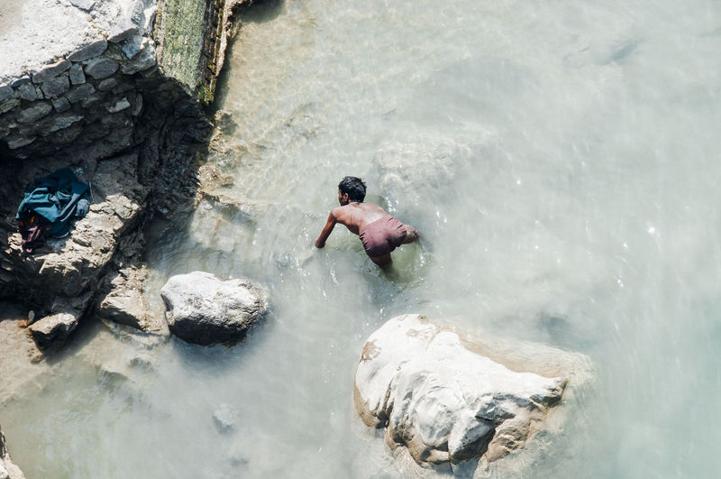 High angle view of shirtless man swimming in water